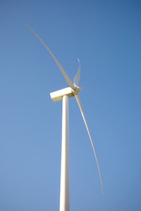 Wind turbine generating electricity over blue sky background