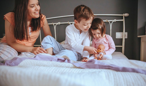 Children feeding doll with cookie sitting over the bed