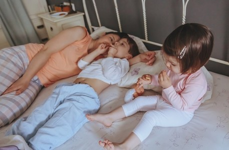 Relaxed children eating cookies over the bed