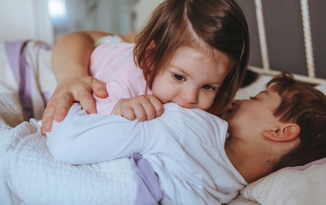 Little girl playing over boy lying in the bed