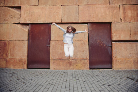 Portrait of happy young woman jumping outdoors