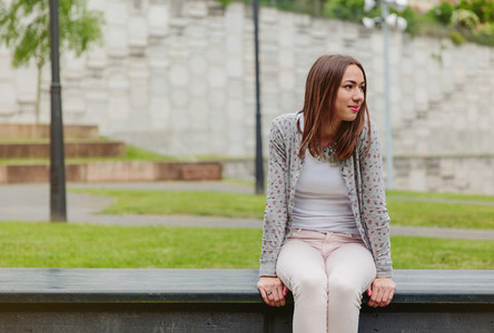 Beautiful young woman sitting on park bench
