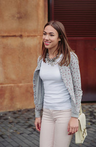 Fashion portrait of young trendy woman walking outdoors