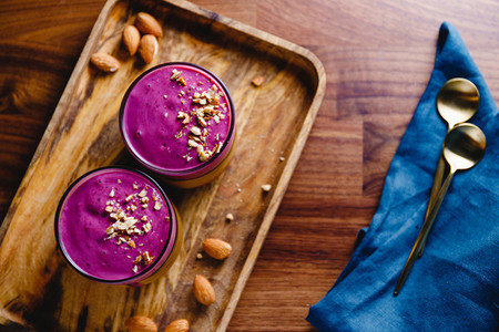 Top view of two glasses with violet berry smoothie are served crushed almond on a wooden tray