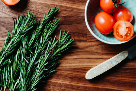 Lifestyle photo of cooking healthy eating with tomatoes and fresh rosemary on a kitchen table