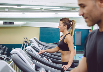 Woman setting control panel of treadmill for training