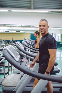 Man warming up in treadmill on fitness center