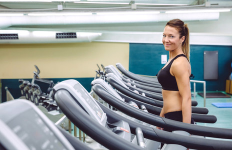 Woman warming up over treadmill in training session