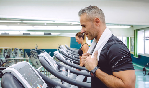 Man with towel in neck training over treadmill