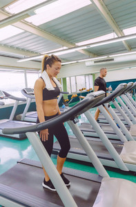 Fitness woman with towel training on a treadmill