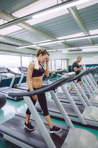 Woman drying with towel while training on treadmill