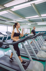 Woman drinking water while training on treadmill