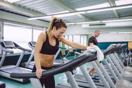 Tired woman resting over treadmill after training