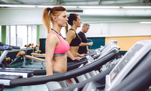 People training over treadmills on fitness center