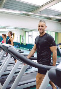 Man with earphones training over a treadmill