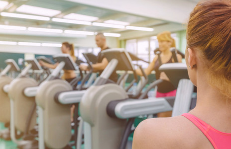 Woman coach looking people in elliptical trainer session