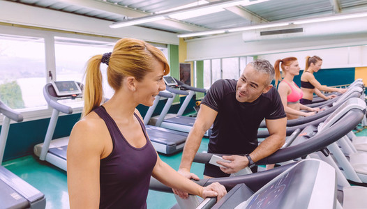 Fitness woman in treadmill talking with hadsome man