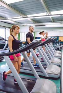 People training over treadmills on fitness center