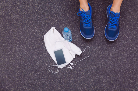 Man legs with sneakers towel water and smartphone in gym floor