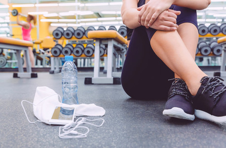 Sporty woman sitting with dumbbells water and smartphone in gym floor