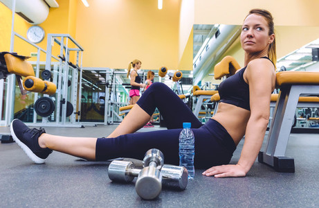 Woman resting and people doing dumbbells exercises on gym