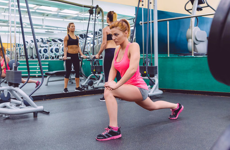 Woman stretching and friend doing dumbbell exercises in gym