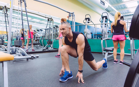 Man stretching and women doing dumbbells exercises in gym