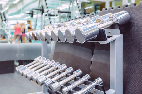 Rows of metal dumbbells in a fitness center
