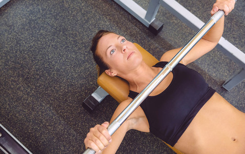 Woman with barbell on a bench press training