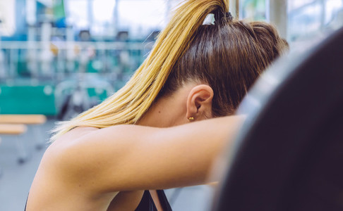 Woman resting tired after lifting barbell on muscular training