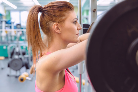 Woman resting after lifting barbell on muscular training