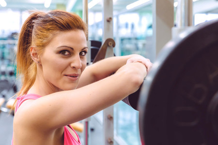 Woman smiling and resting over barbell after training