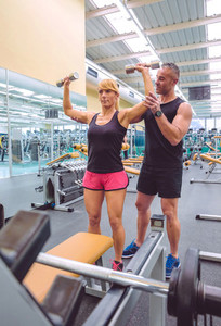 Man coach helping to woman in dumbbells training