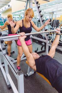 Woman coach encouraging to man in bench press training
