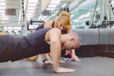 Personal trainer encouraging muscle man in push ups training