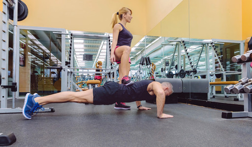 Woman coach training a man with hard push ups