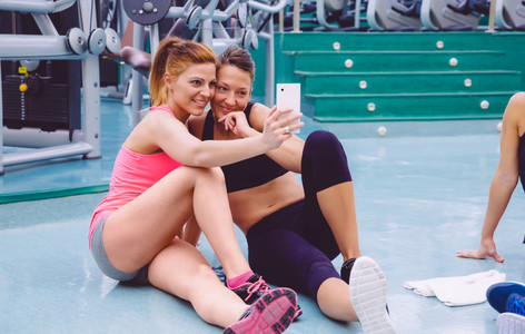 Women friends taking a selfie with the smartphone