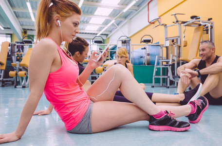 Woman listening music in smartphone and friends talking on the gym