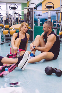 Couple talking on fitness center after training day