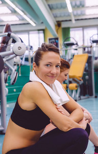 Woman with towel resting in the gym after training