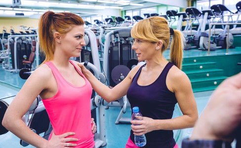 Personal trainer encouraging to sad woman after the training