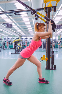 Woman doing suspension training with fitness straps