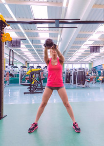 Woman lifting kettlebell in crossfit training