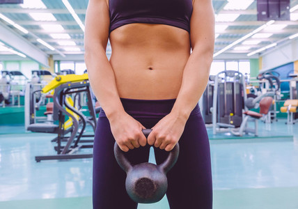 Woman with slim waist and black sportswear holding kettlebell