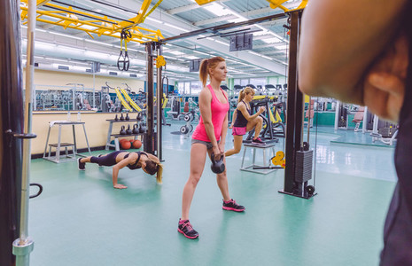 Trainer looking women group training in crossfit circuit
