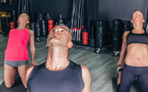 Man doing stretch exercises in fitness class