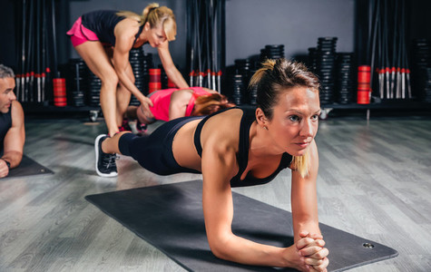 Woman doing push ups with trainer in background