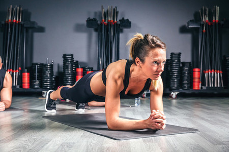 Woman doing push ups in fitness class