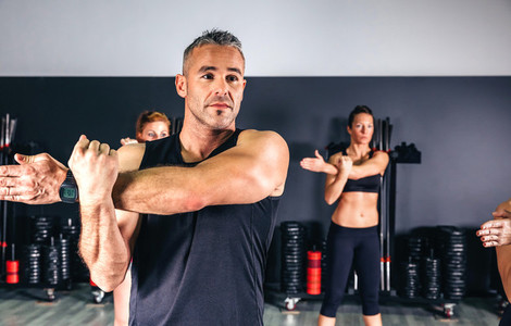 Man stretching his arms in fitness class