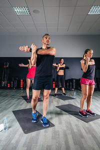People stretching their arms in fitness class